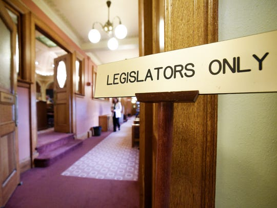 "A sign reading ""Legislators Only"" stands in a hallway"