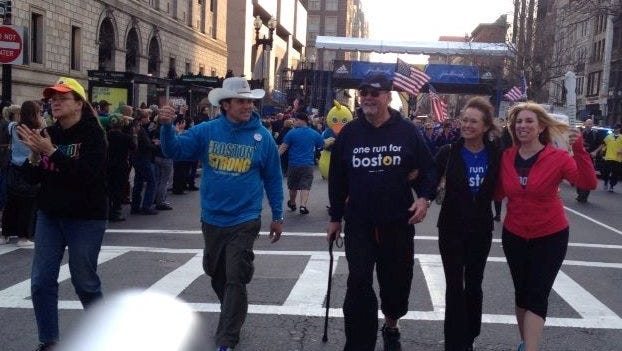 Survivors of the  Boston Marathon bombing April 15, 2013, carry the One Run for Boston baton to the finish on Sunday.