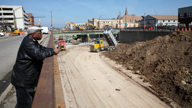 Mike Dukes of Rochester watches the destruction of the bridge on Broad Street and the filling in of the Inner Loop on Monday, April 6, 2015.