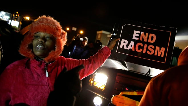 A protester holds up a sign in front of the Ferguson Police Department Tuesday, Nov. 25 in Ferguson, Missouri.
