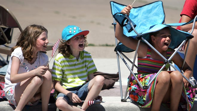 Friends wave flags and found a unique way to keep the sun away as they watch the 62nd Annual Appleton Flag Day Parade along Wisconsin Avenue on Saturday, June 9, 2012 in Appleton, Wisconsin.