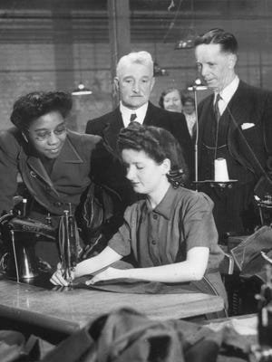 International Ladies' Garment Workers' Union (ILGWU) activist and civil rights leader Maida Springer-Kemp, left observes at sewing machine with others. Photographer: unknown, ca. 1949.  Springer-Kemp joined the ILGWU in 1933 and became the first black agent to oversee an ILGWU district. Among other leadership roles, she served later as educational director in another New York Local, 132. She pushed for integration at union events.