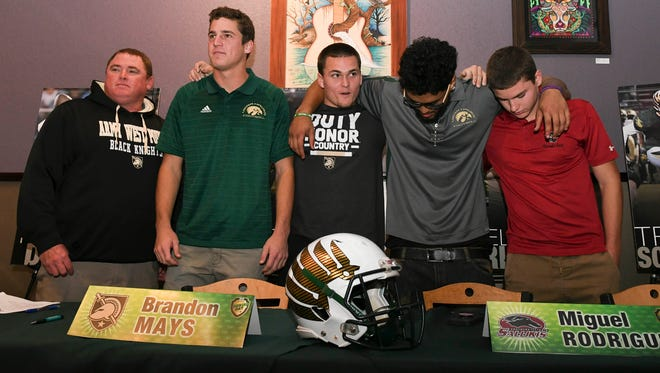 Four Viera players: Tim Demorat, Brandon Mays, Miguel Rodriguez and Trey Schaneville stand with coach Kevin signed their letters of intent today at Pizza Gallery in Viera.