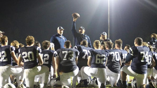 Sault High coach Scott Menard holds up the football as he speaks to the team following a game this past season. Menard is the Upper Peninsula Co-Coach of the Year in the large school division, as voted by the UP Sportswriters and Sportscasters Association.