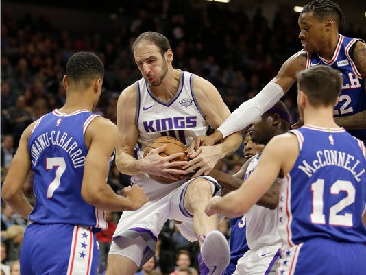Sacramento Kings center Kosta Koufos, second from left, grabs a rebound between Philadelphia 76ers' Timothe Luwawu-Cabarrot, left, T.J. McConnell, front right, and Richaun Holmes, back right, during the first quarter of an NBA basketball game Thursday, Nov. 9, 2017, in Sacramento, Calif. (AP Photo/Rich Pedroncelli)