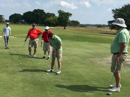 Taylor Rosenthal, center, lines up a putt while playing during a Special Olympics Unified Golf match with his father and teammate, Bill Rosenthal, of Shannon.