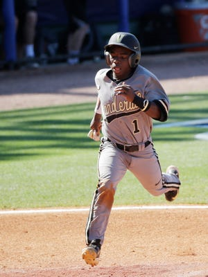 Vanderbilt Ro Coleman jumps toward home plate and scores during the fourth inning.