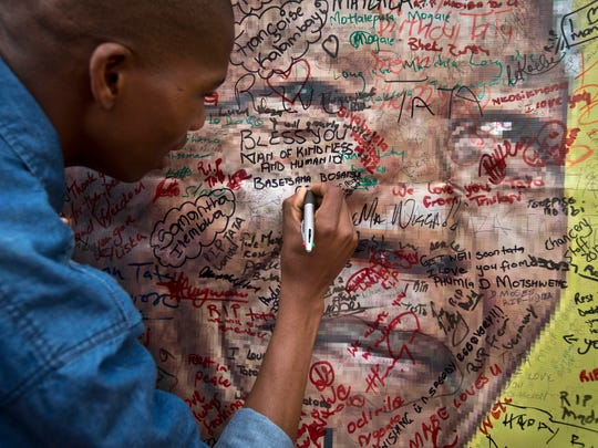 A well-wisher writes a message on a poster of Nelson Mandela on which he and others have written their messages of condolence and support, in the street outside his old house in Soweto, Johannesburg, South Africa. Flags were lowered to half-staff and people in black townships, in upscale mostly white suburbs and in South Africa's vast rural grasslands commemorated Nelson Mandela with song, tears and prayers today while pledging to adhere to the values of unity and democracy that he embodied.