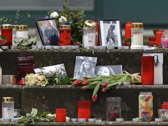 Pictures, flowers and candles are set on the steps to the Joseph-Koenig Gymnasium in Haltern, Germany, Friday, March 27, 2015. Sixteen school children and two teachers from Haltern died in the Germanwings jet airliner crash in the French alps from Barcelona to Duesseldorf on Tuesday. (AP Photo/Martin Meissner)