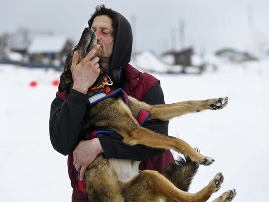 Nicolas Petit hugs one of his dogs before they leave Unalakleet, Alaska, during the Iditarod Trail Sled Dog Race on Sunday, March 10, 2019.
