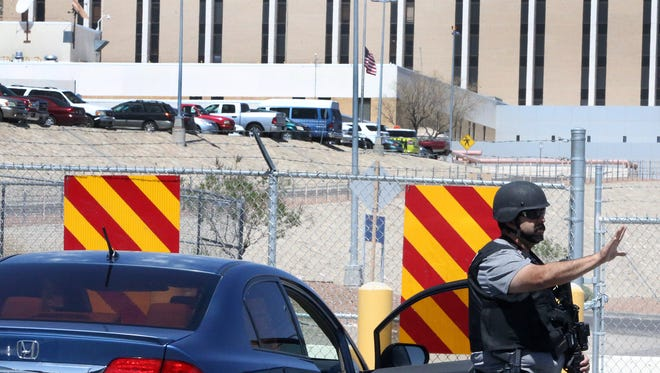 A law enforcement officer halts traffic along Pierce Avenue at the intersection with North Piedras Street behind the El Paso Veterans Affairs outpatient clinic Friday afternoon.