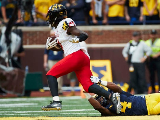 Darnell Savage Jr. breaks a tackle against Michigan after an interception in 2018.