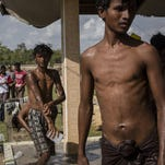 Rohingya and Bangladeshi migrants take a bath after arriving at a port in  Aceh Province, Indonesia, on May 20, 2015.