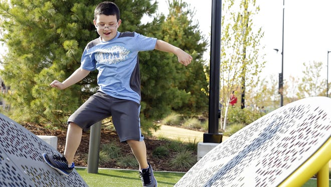 Jaidyn Simon, 9, of Green Bay, plays on a playground obstacle at the Titletown District's plaza and park, which opened to the public Sept. 15.