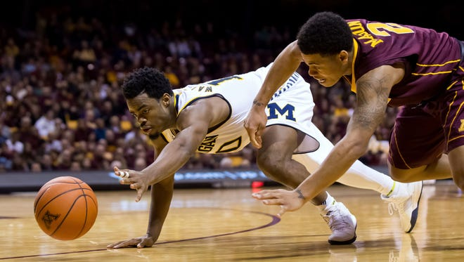 Michigan guard Derrick Walton Jr. (10) and Minnesota guard Nate Mason (2) dive for a loose ball in the second half of U-M's 82-74 win over Minnesota Wednesday in Minneapolis.