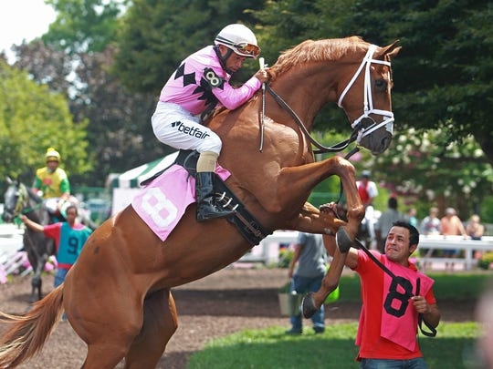 Jockey Jose Ferrer holds on tight as his mount Victory Tour rears up in the paddock at Monmouth Park in Oceanport. Ferrer went on to win the race for trainer Jason Servis.