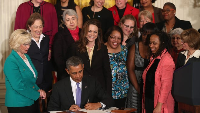 President Obama signs an executive order banning federal contractors from retaliating against employees during an event in the East Room of the White House.