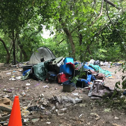Trash piles up at a homeless campsite behind properties