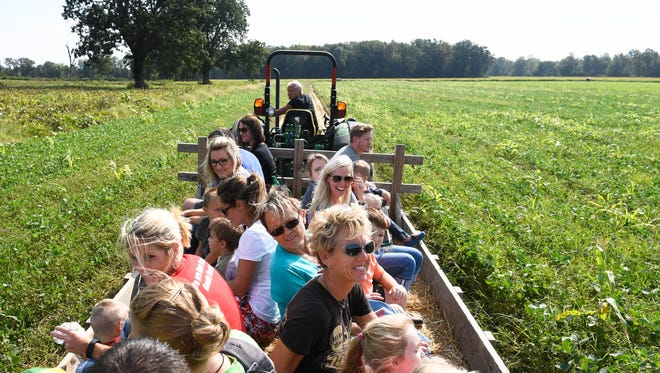 Visitors to the Cates Farm enjoy a hay ride around one of the farm's fields.