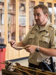 Ranger Wes Williams demonstrates the uses of different artifacts at the Natchez Trace State Park table during 'A Family Affair' Saturday at Lexington High School.