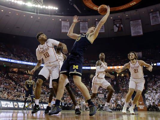 Michigan center Jon Teske (15) grabs a rebound in front of Texas guard Eric Davis Jr. (10) during the first half of an NCAA college basketball game, Tuesday, Dec. 12, 2017, in Austin, Texas. (AP Photo/Eric Gay)