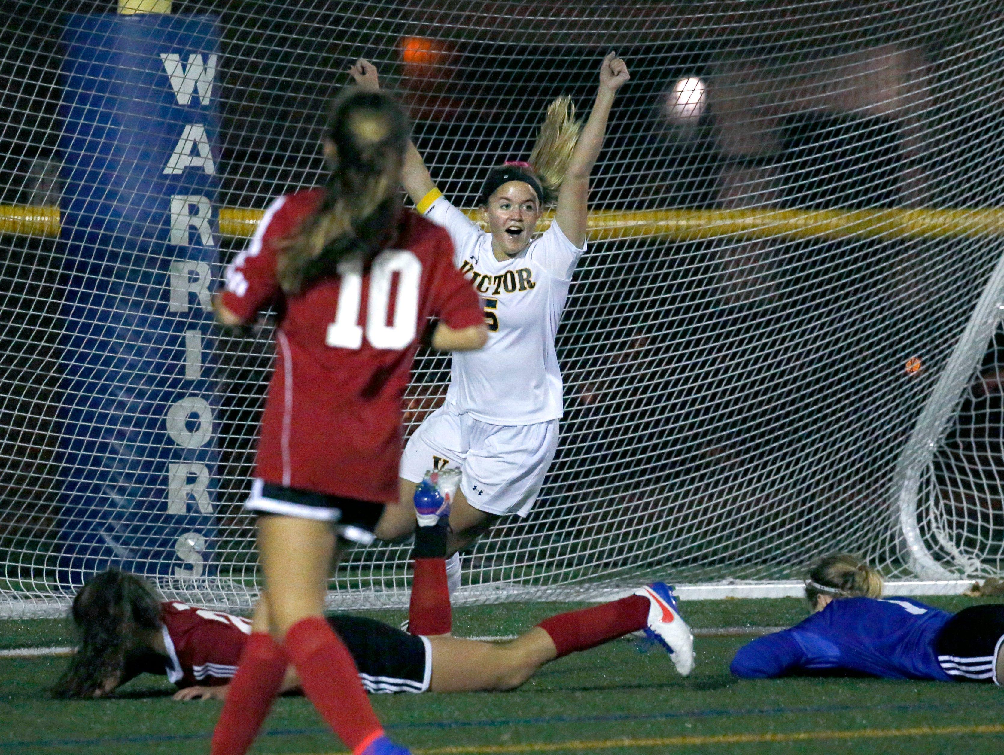 Victor's Anna Schwarzweller celebrates her teammate Lauren Buddendeck's goal to lead Penfield 1-0 in the first half at Webster Schroeder High School.