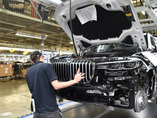 A BMW associate examines a pre-production X7 model
