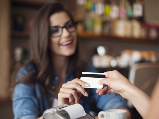 Woman paying with credit card at cafe