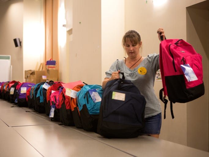 "Volunteer Kierra Jewell lines up backpacks filled with donated school supplies as part of the ""School is Cool"" program to help low-income Poudre School District students this year in Johnson Hall at Colorado State University Wednesday, August 6, 2014. The backpacks contain grade-appropriate supplies and will be delivered to PSD schools in Fort Collins, Wellington, Timnath, and LaPorte, and to outlying mountain schools."