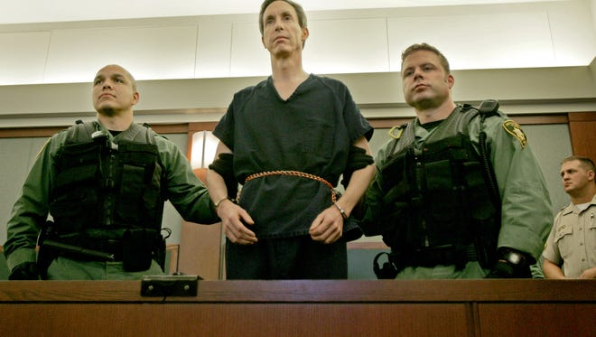 Warren Jeffs stands flanked by two Las Vegas Police officers at the Regional Justice Center in Las Vegas following his arrest in August 2006.