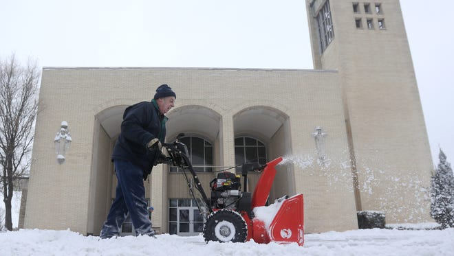 Volunteer Paul Vande Voort clears snow from the entrance to Holy Name of Jesus Church on Wednesday following an overnight snowfall. Wm. Glasheen/USA TODAY NETWORK-Wisconsin.