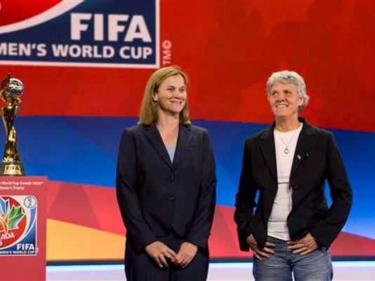 FILE - In this Dec. 6, 2014, file photo, national team soccer coaches, from left, United States coach Jill Ellis and Sweden's coach Pia Sundhage, pose for a photograph in Gatineau, Quebec, after the FIFA Women's World Cup draw.
