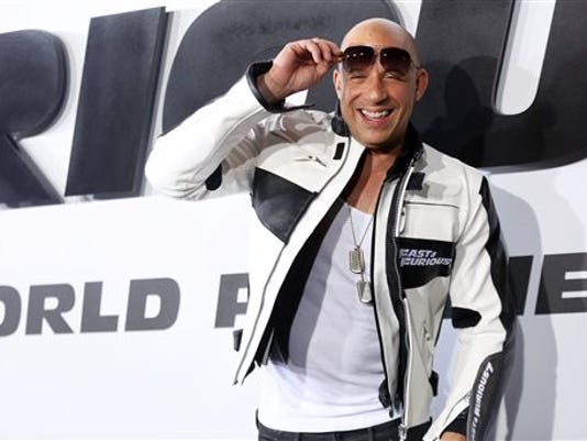 """FILE- In this April 1, 2015, file photo, Vin Diesel arrives at the premiere of """"Furious 7"""" at the TCL Chinese Theatre IMAX on Wednesday, April 1, 2015, in Los Angeles. The reigning box office champion might have slowed from its blockbuster debut, but """"Furious 7"""" maintained first place for the third weekend in a row with an estimated $29.1 million, according to box office tracker Rentrak on Sunday, April 19, 2015. (Photo by Matt Sayles/Invision/AP, File)"""