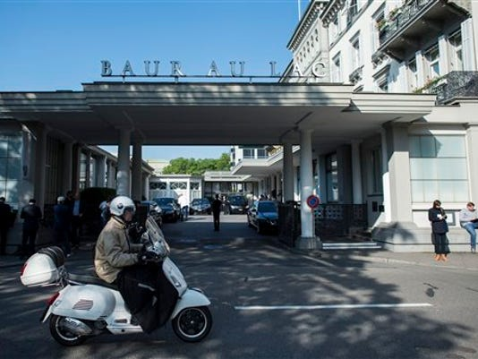 A man on a scooter rides past the five-star hotel Baur au Lac in Zurich, Switzerland, Wednesday morning, May 27, 2015. The Swiss Federal Office of Justice said six soccer officials have been arrested and detained pending extradition at  the request of U.S. authorities ahead of the FIFA congress in Zurich. In a statement Wednesday the FOJ said U.S. authorities suspect the officials of having received paid bribes totaling millions of dollars.