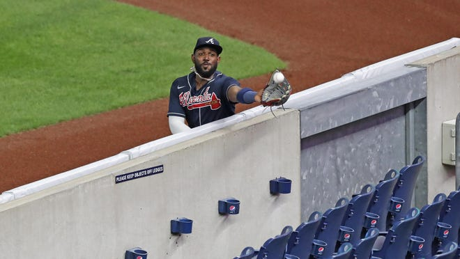 Atlanta Braves right fielder Marcell Ozuna tries to catch a foul fly ball but comes up short as it bounces in the empty stands during an August game against the New York Yankees. Supporters say sports betting could regenerate interest in pro sports at a time COVID-19 has emptied the stands.