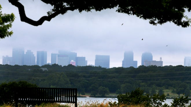 Clouds linger over the skyline of Dallas in this file photo from 2014.