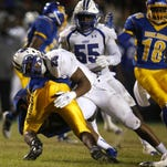 Lincoln's Casey Warming tackles Rickards' DJ Phillips as he tries to break the plane of the goal line during their game at Cox Stadium last season.