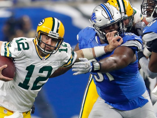 Green Bay Packers quarterback Aaron Rodgers stiff-arms Detroit Lions defensive tackle A'Shawn Robinson (91) on Jan. 1, 2017, in Detroit.