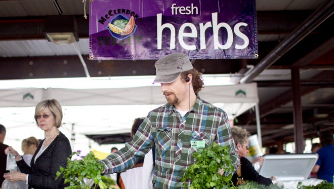 Chef Payton Curry sets out fresh herbs at the Old Town Farmers Market in Scottsdale.