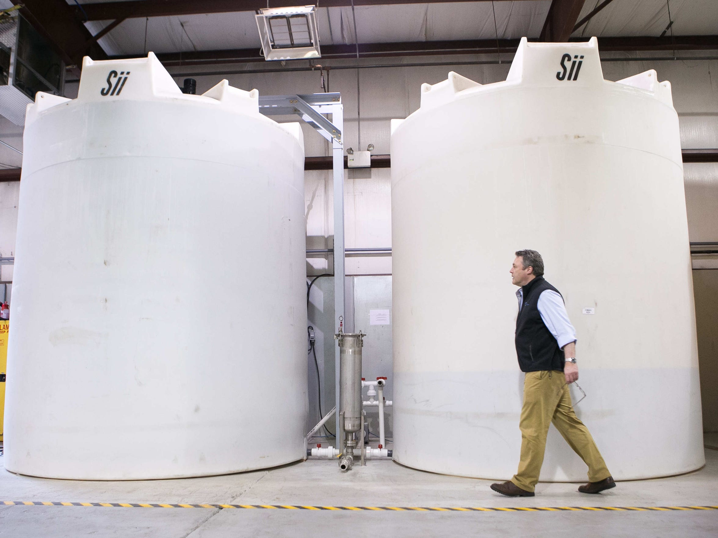 EnviroKure CEO Mark Lupke walks by tanks storing up to 6,500 gallons of liquid fertilizer. The startup plans to open a facility in Harrington next year where poultry poop will be converted into liquid fertilizer.