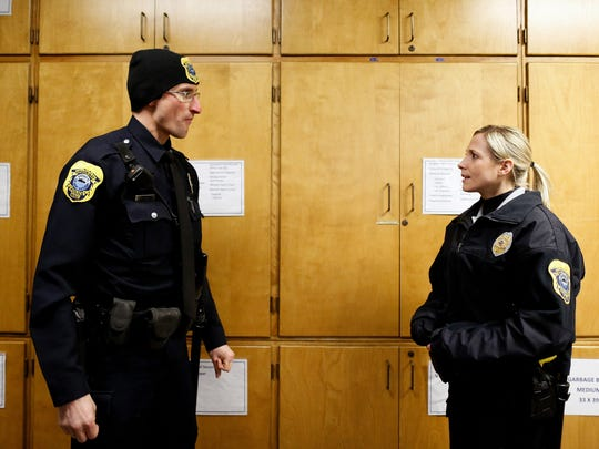 Green Bay Police Officer Tom Behn speaks with Officer Tracy Liska about an incident with a person facing eviction.