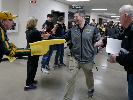 UW-Oshkosh coach Pat Juckem walks through a fan tunnel as faculty, staff, students and fans gathered Wednesday at Kolf Sports Center  to send off the men's basketball team.