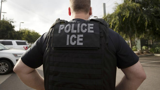 In this July 8 file photo, a U.S. Immigration and Customs Enforcement officer looks on during an operation in Escondido, Calif. ICE officials on Friday changed the rules for international students again, saying those who are newly-enrolling will not be allowed to enter the U.S. if their universities are entirely online.