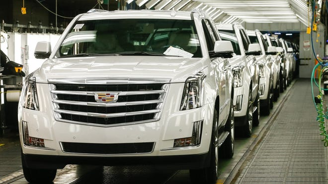 Cadillacs are seen on the assembly line.
