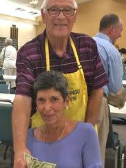Marvin Klein of the JCMI Bingo Committee hands Carol