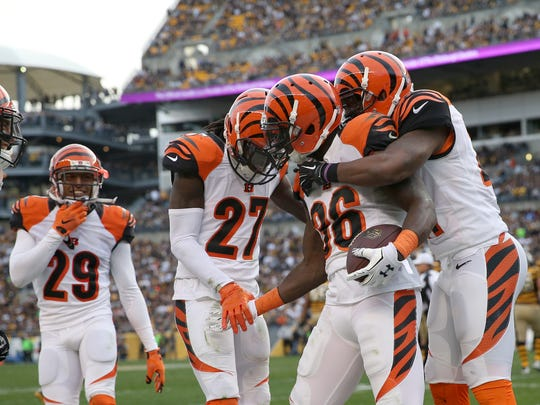 Bengals strong safety Shawn Williams (center) is congratulated by teammates after his interception at Pittsburgh, arguably the biggest play of the year for the Cincinnati defense.