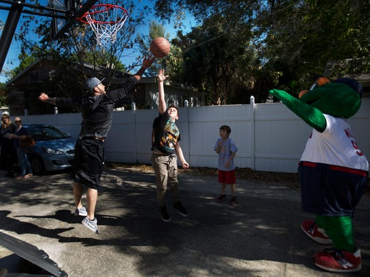 Blake Swihart, a catcher for the Boston Red Sox plays a game of basketball with Eddie Powers,14,  and Slater Smith,8, at Valerie's House in Fort Myers.  Swihart was with a group of Red Sox players including Wally the mascot who brightened the day of children who have lost a parent or sibling.