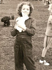 A girl catches a live bunny at the 1953 West Side Nut