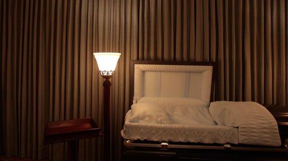 A light illuminates an empty casket in a funeral parlor.