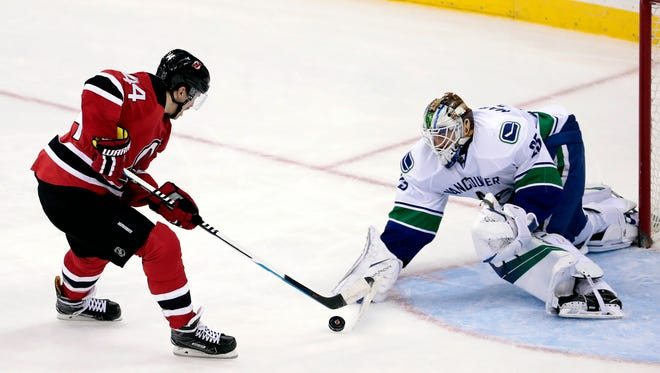 New Jersey Devils' Miles Wood, left, attacks against Vancouver Canucks goalie Jacob Markstrom during Tuesday's game.